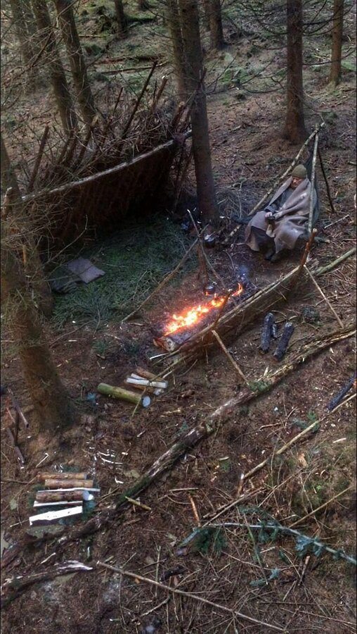 Lean-to shelter with bough bed, a tripod chair, and a long fire #survivalshelter.jpg